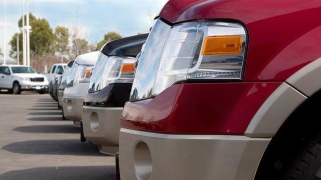 lineup of Ford pickup trucks on car dealership lot