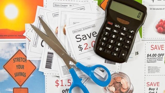 coupons in sales ads advertisements with calculator and scissors