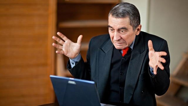 shocked businessman looking at laptop computer