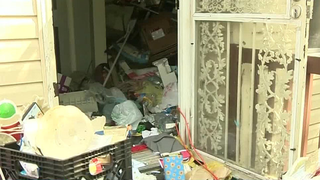 Trash piled by door of filthy house on Detroit's west side