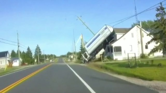 Video shows truck pinned between house, pole in Canada