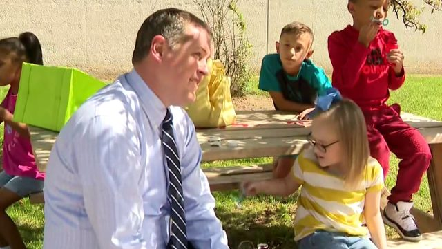 Romulus principal plays with child with cerebral palsy who was alone at recess